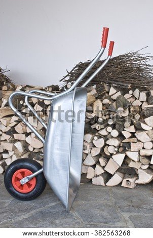 The empty wheelbarrow, standing next to the woodshed - stock photo