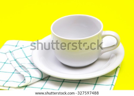 the  empty white coffee or tea cup with towel on vibrant color background - stock photo
