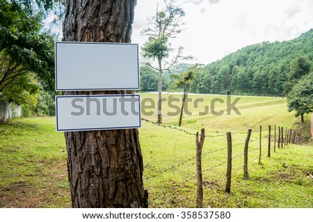 The empty white labels that is stuck at a tree with green pastures Background / Horizontal