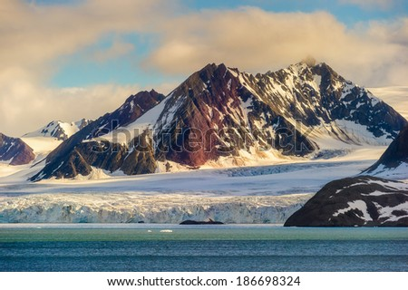 The end of a glacier in the Arctic Circle where it falls into the Arctic Ocean in Hornsund, Svalbard, Norway. - stock photo