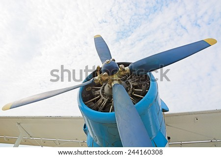 The engine and propeller plane AN2 close-up on a background of blue sky and clouds. The picture at the low point. - stock photo