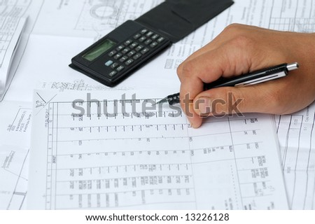 The engineer checks calculations in drawings.