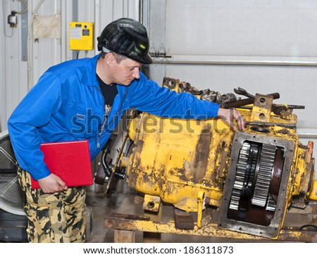 The engineer checks the transmission mechanism.