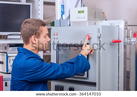 The engineer presses a button in a scientific laboratory during the experiment
