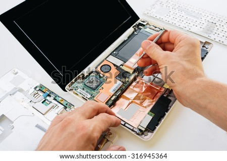 The engineer repairs the laptop (pc, computer) and the motherboard. Installs the equipment (cpu) - stock photo