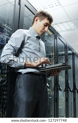 The engineer stand in data center near telecommunication equipment with tablet PC - stock photo