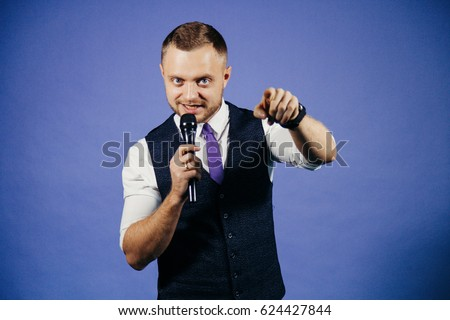 The entertainer. Young elegant talking man holding microphone, Isolated on blue background
