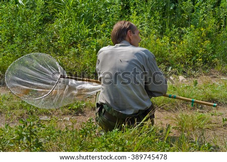 The entomologist with butterfly-net on meadow. - stock photo