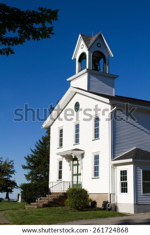 The entrance of an old white country church with a bell tower sits on a hill with a blue sky background.