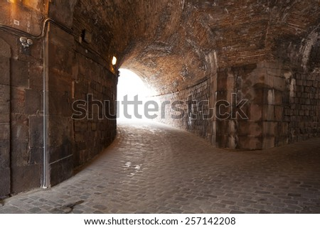 The entrance of fortress Montjuïc, Castel in Barcelona, Spain, with lights coming through from behind - stock photo