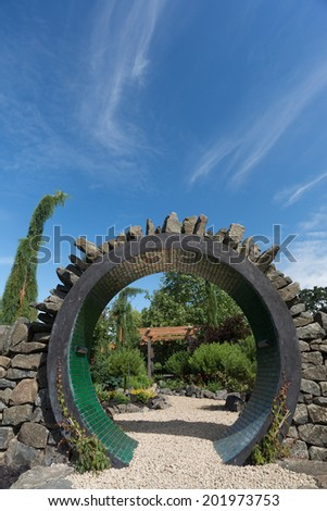 The entrance to a Japanese Influenced arbor can be seen through the circular entrance to this perennial garden surrounded by a dry fit stone wall.