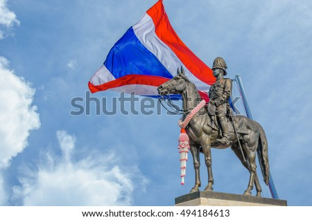 The Equestrian Statue of King Rama V in Bangkok Thailand whit Thailand flag on cloudy and blue sky background