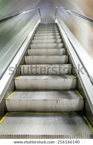 The escalator in the business center rises to the top - stock photo