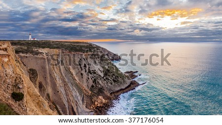 The Espichel Cape, with the 18th century lighthouse and a view over the Atlantic Ocean during sunset. Sesimbra, Portugal. - stock photo