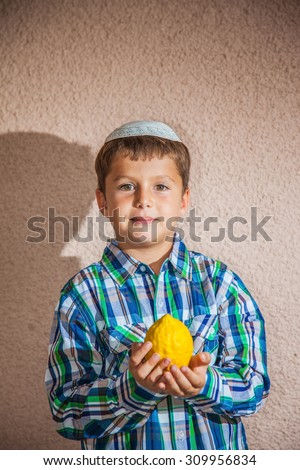 The etrog - ritual fruit for Jewish holiday of Sukkot. The charming seven-year-old boy in white festive skullcap holds citrus in hand - stock photo