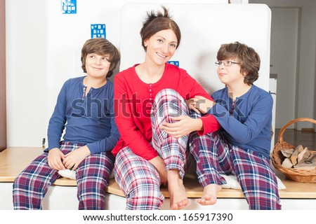 The European family, mother and two sons, in pajamas, sitting on the stove, smiling, one son looking at mom, the second looks away - stock photo