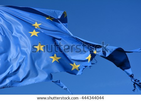 The european union twelve star flag torn and with knots in the wind on blue sky