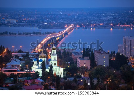 the evening city of Saratov with the bridge through the Volga River - stock photo