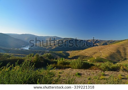 The evening sun lights the hills overlooking the River Douro in northern Portugal. A region famous for its wine making - stock photo