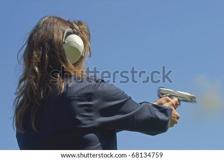 the exact instant a handgun lets a bullet flie - stock photo