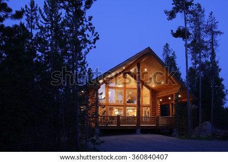 The exterior at dusk of a modern log cabin, in the mountains.
