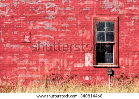 The exterior wall on the side of an old red building with a broken window. - stock photo
