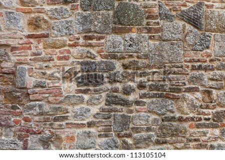 The facade view of the old brick wall in tuscan city Montepulciano for design background. - stock photo