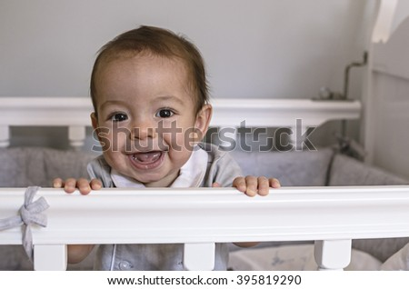 The face of a cute happy baby, boy smiling in wooden cot or crib. - stock photo