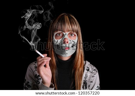 The face of a young woman smoker, holding a cigarette in her hand