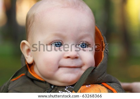 The face of the one-year-old child on a green background, a close up - stock photo