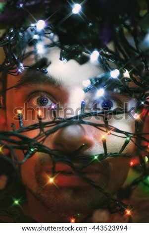The face of young man with Christmas lights