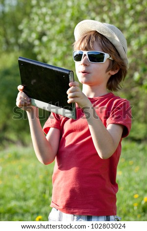 The fair-haired boy plays in the Tablet PC sunny day - stock photo
