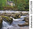 The Falls of Dochart, spectacular waterfalls and white water rapids on the River Dochart as it flows through dense woodland in the village of Killin, near Loch Tay in the Scottish Highlands. - stock photo