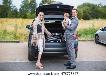The family business with a child in her arms near a black car on yard. Young couple standing near the opened car boot with suitcases, looking to the camera, outdoors