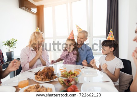 The family congratulates the little girl on her birthday. The girl is sitting at the festive table. She is delighted with her congratulations