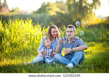The family father, mother and son smiling and spend time together on the bright green grass.