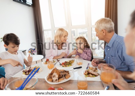 The family is having supper at the festive table for Thanksgiving. Grandma offers a granddaughter who sits next to try the grapes