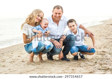 The family of a man a woman and two children walking on the beach and breathe the sea air