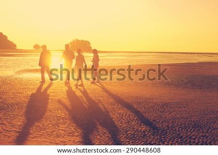 The family walking at the beach during sunset time, orange sun light, like instagram filter effect - stock photo