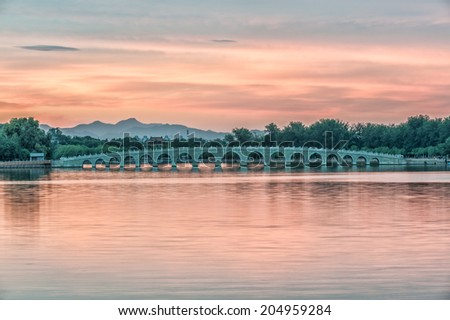 The Famous 17 arch lion bridge in Summer Palace under the sunset outside of Beijing, China. - stock photo