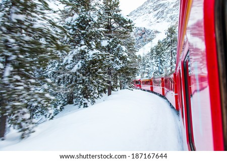 The famous Bernina red train, Unesco monument, in the middle of a winter storm - stock photo