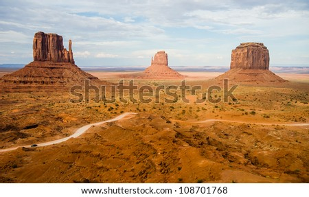 The famous Buttes of Monument Valley Navajo National park, Utah, USA with car driving dirt road giving perspective of huge scale of the Buttes and the Valley - stock photo