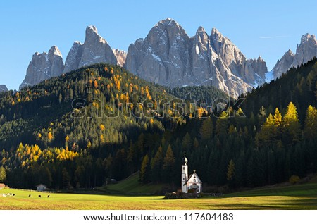 The famous church of San Giovanni in Ranui (Sankt Johann) in front of the Geisler or Odle dolomites mountain peaks in Santa Maddalena (Sankt Magdalena) in the Val di Funes in Italy.