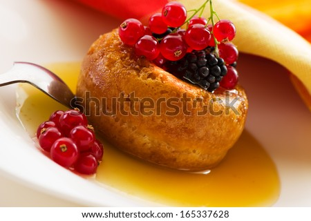The famous Italian sweet Baba of Naples with rum syrup with fresh backberry and currant - stock photo