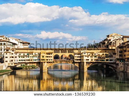 The famous old bridge in Florence which is reflected in the river Arno in Florence gives life to a striking image. - stock photo