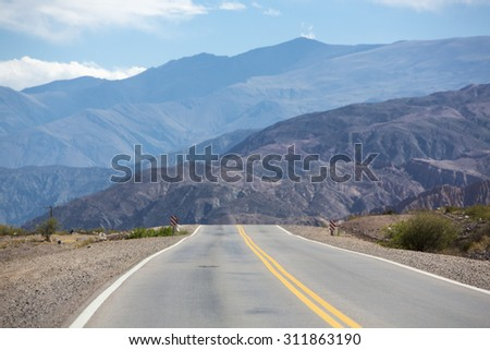 The famous Route 40 paved road parallel to the Andes against a blue sky and going towards the Salinas Grande, Jujuy Province. Argentina 2014