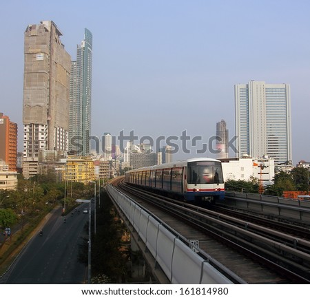 The famous thai skytrain on it's elevated track is speeding through the city of Bangkok. In the background are the towers and skyscrapers of the city. Deep down a few cars and mopeds are visible.