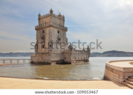 The famous Tower of Belem in the water of the river Tagus. White marble tower is decorated with turrets and battlements in the Moorish style