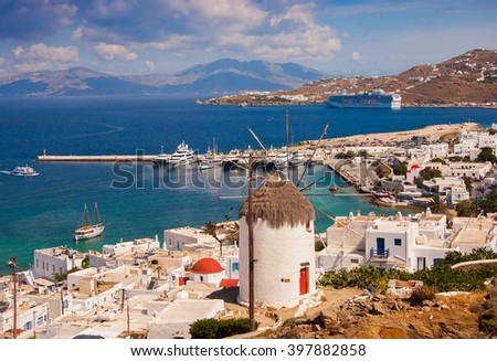 The famous windmill above the town of Mykonos in Greece against the blue sky with clouds. - stock photo