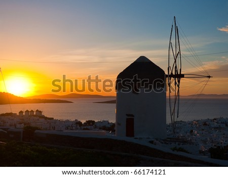 The famous windmill on the side of the island of Mykonos at sunset and views of the town with windmills. - stock photo